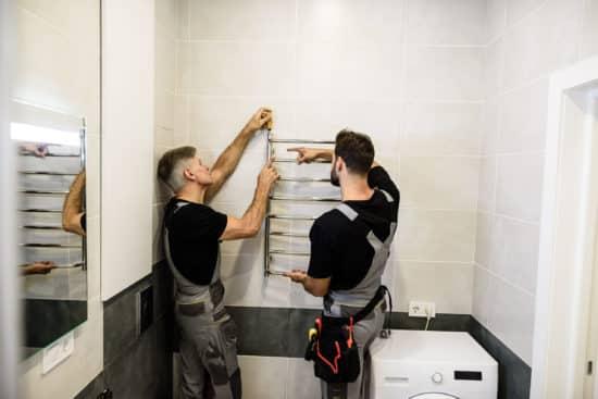plombier le havre - Deux plombiers installent un radiateur