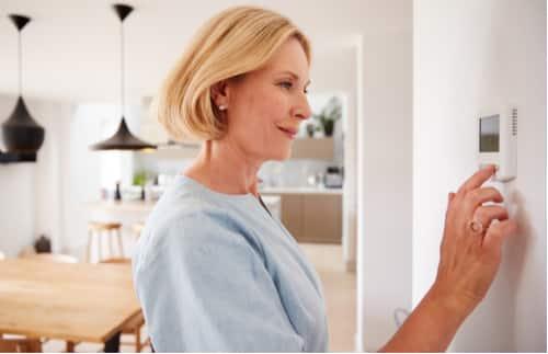 chauffagiste paris - femme réglant son thermostat