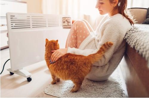 chauffagiste nantes - une femme et son chat devant un radiateur électrique