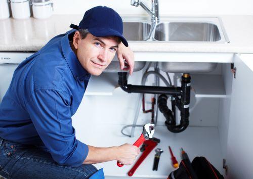 plombier colmar - artisan plombier tenant une clé de serrage