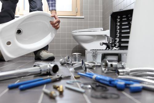 un artisan installe les appareils sanitaires dans une salle de bains