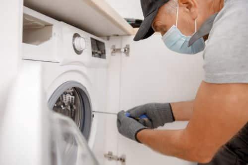 plombier Colombes - un artisan installe une machine à laver