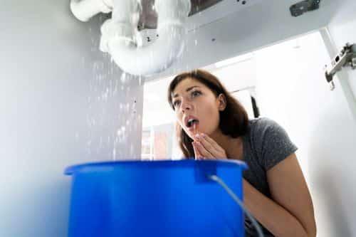 plombier Créteil - une femme constate une fuite de son évier