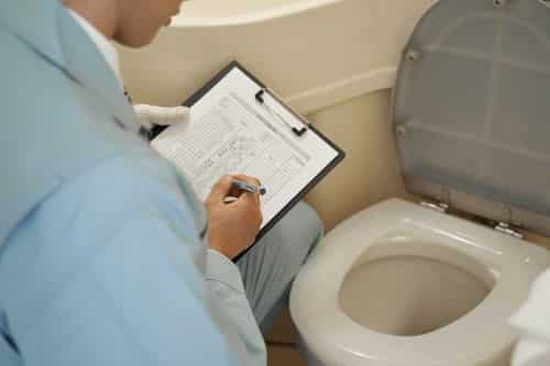 plombier Créteil - un artisan inspecte des toilettes