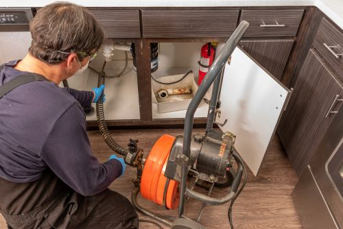 plombier Nanterre - un artisan débouche un tuyau