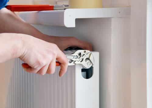 plombier Toulouse - un plombier purge un radiateur