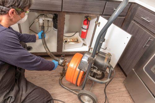 plombier Versailles - un artisan débouche une canalisation au furet électrique