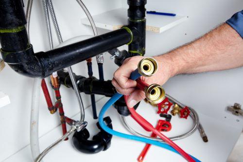 plombier Villejuif - un artisan tient 2 flexibles, un bleu et un rouge