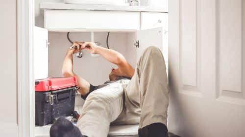 plombier argenteuil - un plombier installe un siphon d'évier