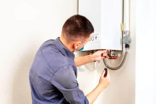 Plombier Antibes - Un plombier répare un ballon d'eau chaude