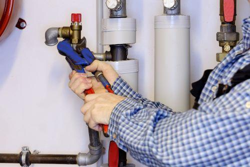 Plombier Antibes - Un artisan plombier vérifie des raccords de tuyauterie.