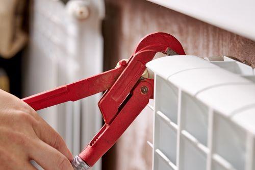 plombier Bayonne - Un artisan répare un radiateur à l'aide d'une clé de serrage.