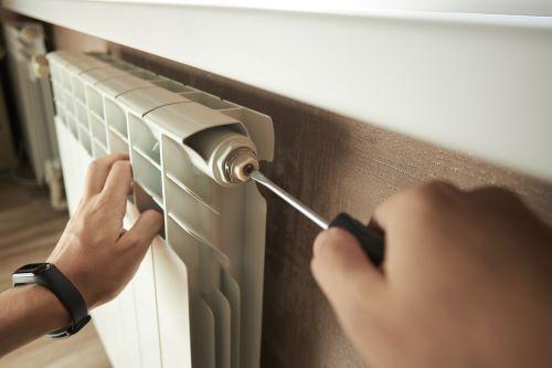 plombier Bayonne - Un technicien plombier répare et purge un radiateur à eau.