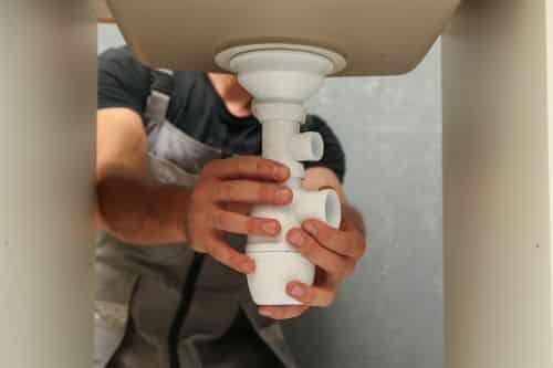 Plombier Cagnes-sur-Mer - Un plombier installe le siphon d'un évier de cuisine.