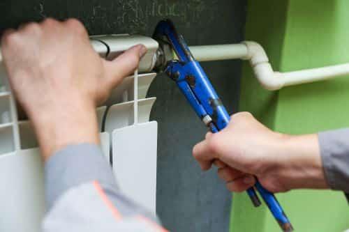 Plombier Cagnes-sur-Mer - Un artisan plombier répare un radiateur avec un outil.
