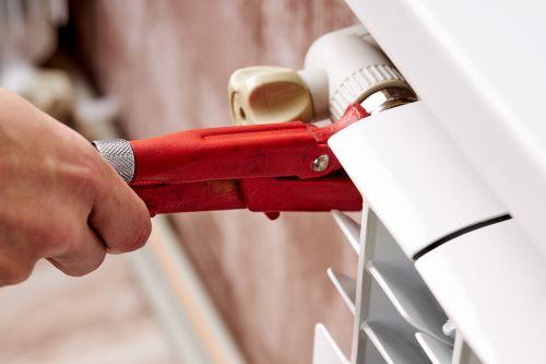 Plombier Châtenay-Malabry - Un artisan plombier répare un radiateur en panne.