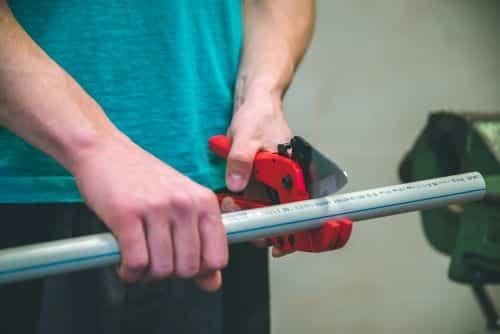 Plombier Cholet - Un plombier coupe des tuyaux en plastique polypropylène avec des ciseaux pour souder un conduit d'eau.