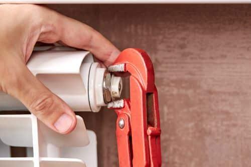 Plombier Fréjus - Un artisan purge un radiateur.