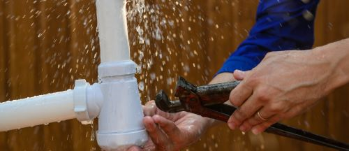 Plombier Montauban - Un plombier répare un tuyau qui est en train de fuir.
