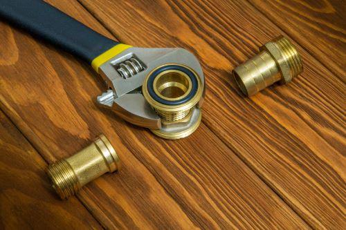 Plombier Montigny-le-Bretonneux - Raccords de plomberie en laiton avec une clé à molette.
