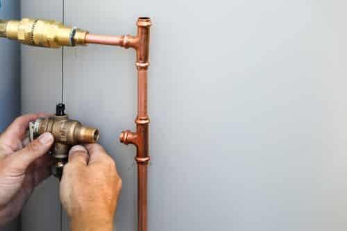 Plombier Narbonne - Un artisan en train d'installer un ballon d'eau chaude électrique.