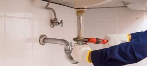 Plombier Pessac - Un plombier avec une clé de serrage