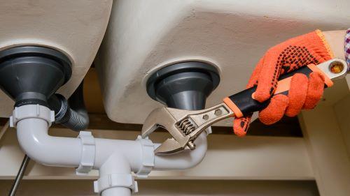 Plombier Quimper - Un plombier intervient sur des tuyaux avec une clé de serrage