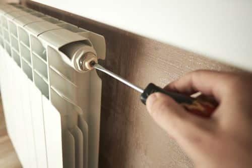 plombier Saint-Martin-d'Hères - Un artisan répare un radiateur.