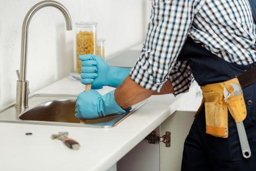 Plombier Saint-Quentin - Un plombier en train de déboucher un évier de cuisine.
