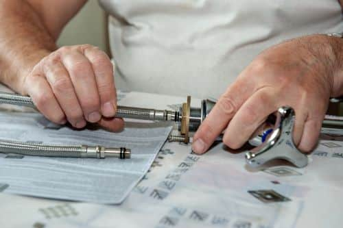 Plombier Tourcoing - Un plombier installe un mitigeur.