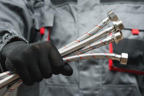 Plombier Valence 1 - Un plombier tient dans sa main des tuyaux flexibles.