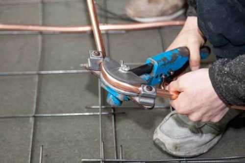 Plombier Vannes - Un artisan tord un tuyau en cuivre.