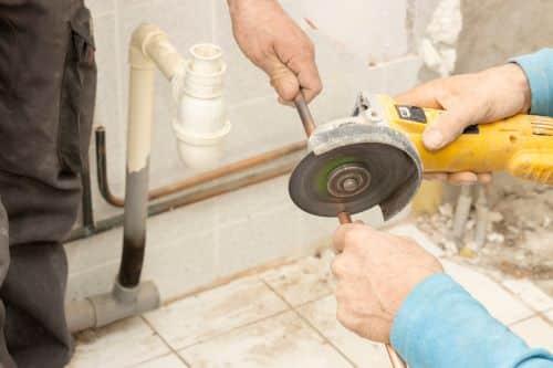 Plombier Villeneuve-d'Ascq - L'artisan coupe un tube en cuivre à la scie circulaire