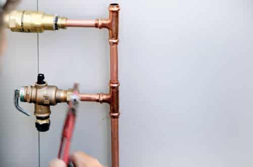 Plombier Villeneuve-d'Ascq - Un artisan intervient sur un circuit de tuyaux en cuivre