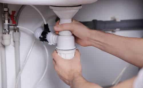 plombier Bagneux - un artisan dévisse le siphon d'un lavabo