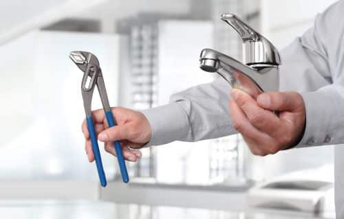 plombier Châtillon - un homme montre un robinet et une pince