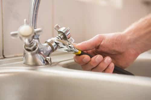 plombier Corbeil-Essonnes - un artisan resserre le robinet d'un évier
