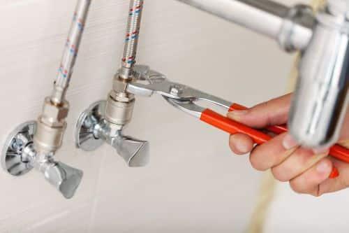 plombier Fontenay-sous-Bois - un plombier installe un flexible de lavabo