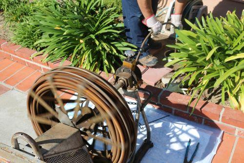 plombier Gagny - un artisan débouche une canalisation extérieure avec un furet électrique