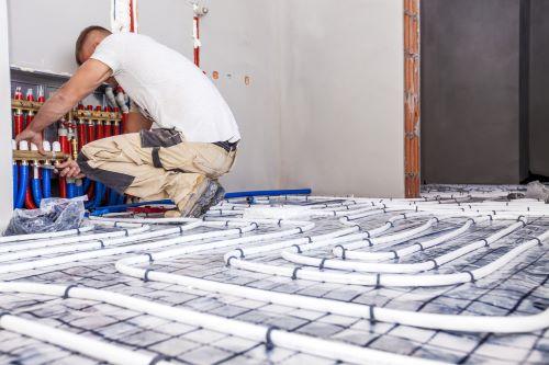 plombier Meudon - un artisan installe un plancher chauffant