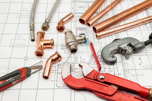 plombier Pantin - des élément de tuyauterie en cuivre sur un plan d'architecte