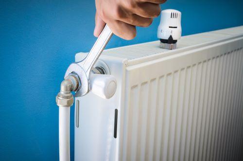 plombier Puteaux - un artisan change la tête de robinet du radiateur