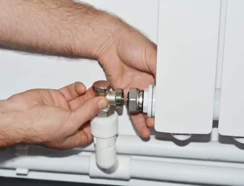 Plombier Roubaix - Un plombier raccorde un radiateur.