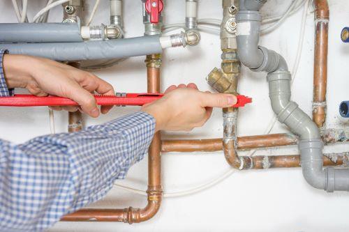 plombier Sartrouville - un plombier installe une tuyauterie en cuivre
