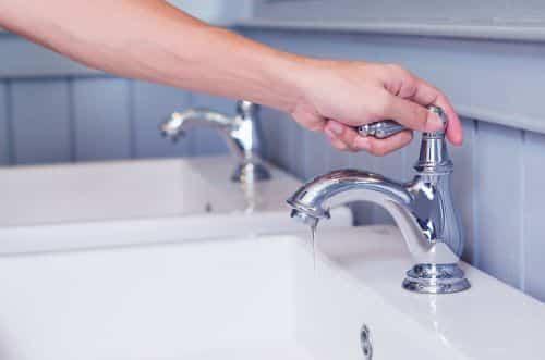 plombier Savigny-sur-Orge - une femme vérifie le fonctionnement du robinet