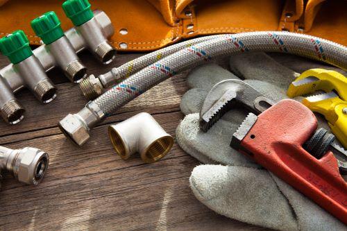 plombier Stains - des éléments de plomberie à côté de clés de serrage