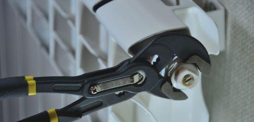 Plombier Albi - Un plombier répare un radiateur.