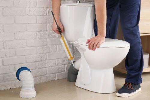 Plombier Alès - Un artisan mets des joints sur une sortie de toilettes.