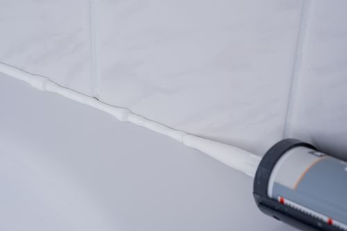 Plombier Angoulême - Application d'un joint sur les angles d'une salle de bains.