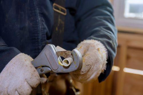 Plombier Arras - Un artisan coupe un tuyau en PVC.